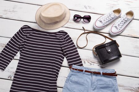 Striped top and sunglasses. Beige hat and white shoes. Rubber shoes and casual clothing. Womans fashionable spring outfit.