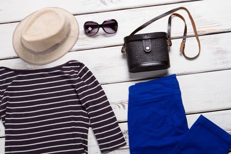 Beige hat and black purse. Navy pants and sunglasses. Female accessories on white shelf. Set of clothes for spring.