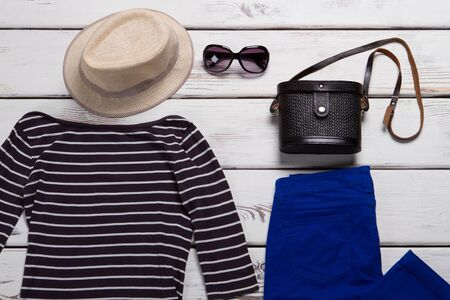 Beige hat and blue pants. Dark sunglasses and striped top. Girls apparel from spring collection. Special offer at shopping mall.