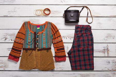 Embroidered top with long sleeves. Checkered pants and black bag. Womans apparel and vintage purse. Stay true to your style. Zdjęcie Seryjne