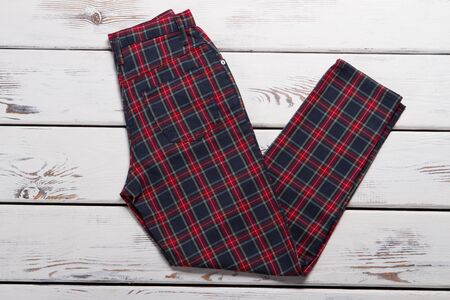Black and red chekered pants. Folded trousers on wooden background. Ladys casual pants for spring. New garment in boutique.