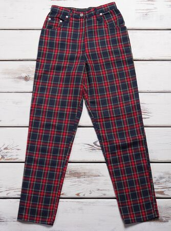 Red and black chekered pants. Trousers on white wooden background. New clothing item on sale. Trendy female pants.