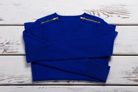 Blue folded sweater. Womans casual navy pullover. Woolen garment on white shelf. New item of high quality. Stockfoto