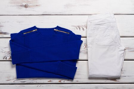 Blue folded sweater and pants. White trousers and pullover. Ladys clothes for autumn. Clothing items from new catalog.