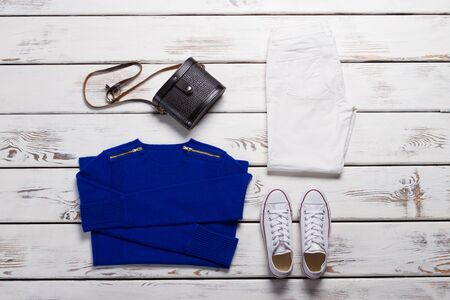 Folded sweatshirt and white shoes. Black purse and blue pullover. Stylish female outfit for autumn. New items in showroom.