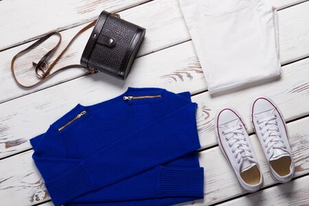 Folded sweater and white shoes. Blue sweatshirt and dark purse. Girls comfortable spring clothing. Stylish clothes in showroom.