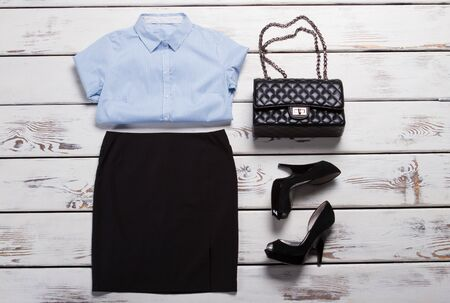 Folded shirt and black skirt. Dark clutch bag and heels. Womans casual evening outfit. New arrivals in brand store. Zdjęcie Seryjne
