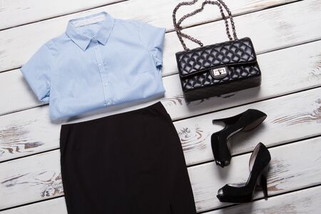 Striped shirt and black skirt. Heel shoes and light shirt. Clutch bag with chain strap. Elegant clothes and luxury accessory.