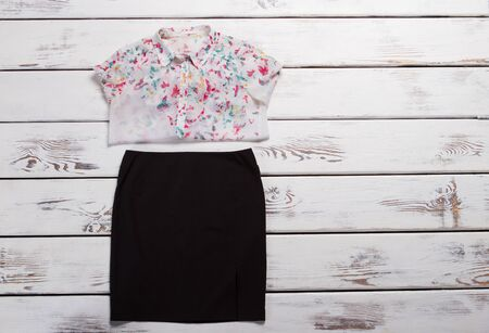 Light shirt and black skirt. Folded shirt with colorful print. Girls evening clothes on shelf. Clothing items in brand store.