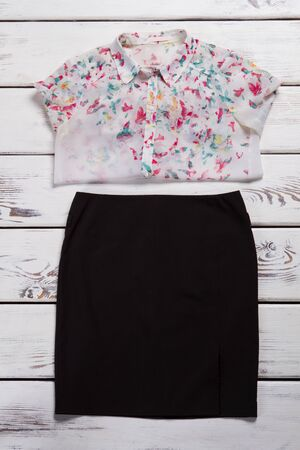 Skirt and shirt with print. Black skirt on wooden background. Womans shirt with butterfly print. Designer clothes in shopping mall. Zdjęcie Seryjne
