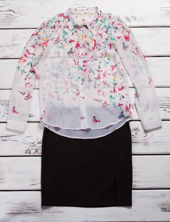 Shirt with print and skirt. White shirt with colorful print. Clothing sale in brand store. Ladys fashionable clothes for spring.