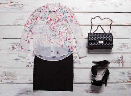 Shirt with print and purse. Black heel shoes and skirt. Quilted leather clutch bag. Luxury female apparel in showroom.