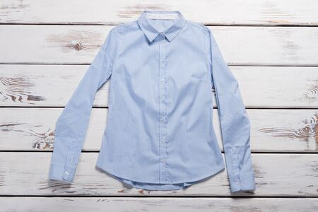 Light blue formal shirt. Striped shirt on wooden background. Work-appropriate shirt for ladies. Quality item in clothing store. Zdjęcie Seryjne