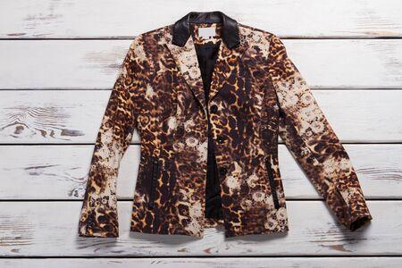 Girls leopard blazer. Leopard blazer on wooden background. Exclusive garment from boutique. Luxury and originality.