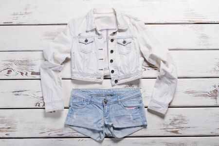 Short jacket and denim shorts. Blue shorts and white jacket. Trendy clothes for young girls. New items in jeans shop.