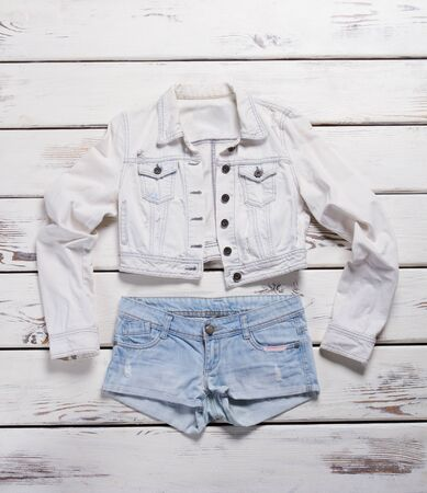 Jacket and light blue shorts. Denim shorts and white jacket. Womans light summer apparel. Quality items from jeans store.