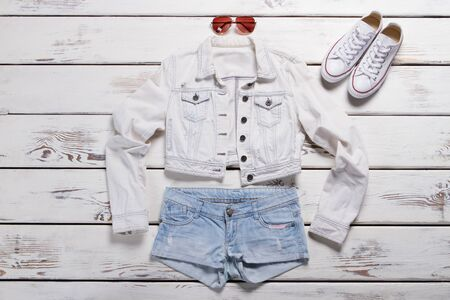 Short jacket and white shoes. Denim shorts and sunglasses. Classy spring outfit for ladies. Clothing purchased in brand shop.