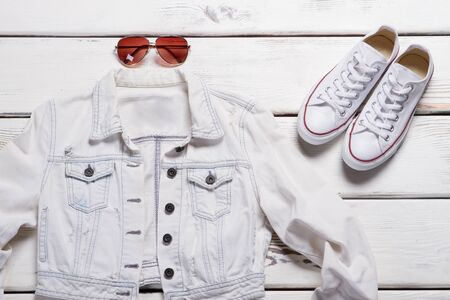 Short white jacket and sunglasses. White footwear and jacket. Clothing sale in outlet store. Female aviator sunglasses. Zdjęcie Seryjne