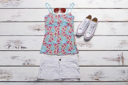 Summer top and white skirt. Colorful top and sunglasses. Womans blue top with print. New clothing items on table. Stockfoto