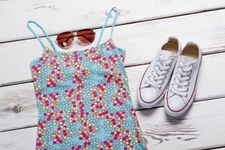 Blue top with colorful print. Sunglasses and white shoes. Ladys clothes on wooden shelf. Best prices for summer clothing. Stockfoto