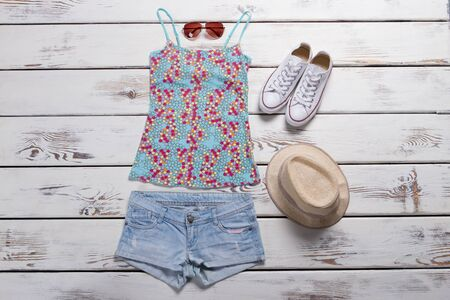 Top with print and shorts. Blue shorts and beige hat. Female outfit with trendy hat. Clothes from internet shop. Stock Photo