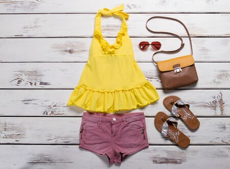 Yellow top, pink shorts and accessories on wooden background. A set of summer clothes. Stock Photo
