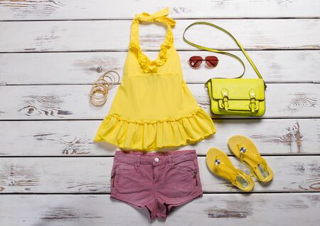 Bright summer outfit. Bright yellow top and pink shorts. Lime bag with yellow sandel and accessories.