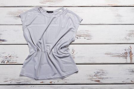 Nylon gray T-shirt on a wooden background. Stylish womens clothing. Summer collection.