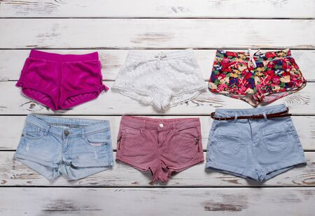 Many different shorts on a wooden background. Summer collection of shorts.