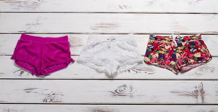 Shorts of different colors and different prints on the wooden background.