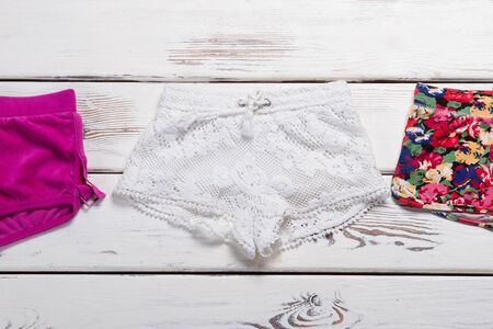 Beautiful white knitted shorts. Collection of new shorts with different prints. Stock Photo