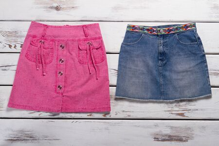 Beautiful denim skirt on a wooden background. Pink and blue skirts for teenagers.