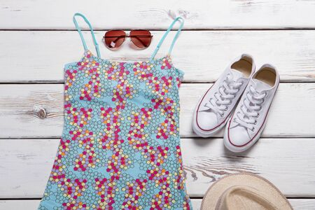 Sleeveless top and sunglasses. Blue top with pink pattern. Girls classic rubber shoes. Summer clothing purchased in boutique.