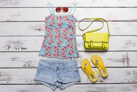 Sleeveless top and blue shorts. Yellow flip flops and bag. Womans colorful summer apparel. Seasonal sale in brand store.