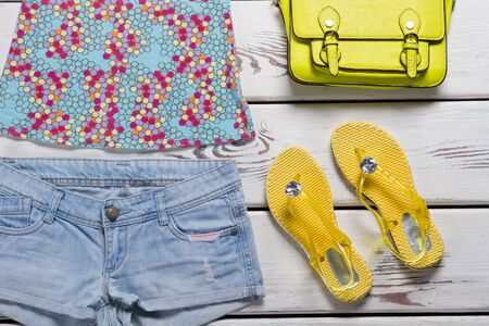 Yellow flip flops and shorts. Blue shorts and lime bag. Ladys casual summer footwear. Stylish clothing from outlet shop.