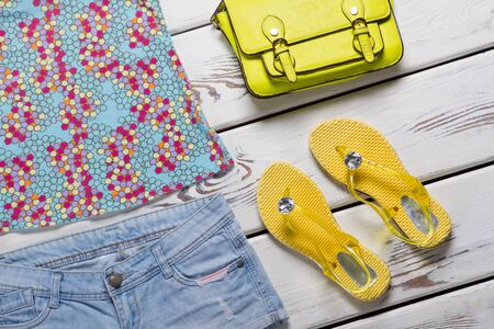 Shorts and yellow flip flops. Lime bag and summer footwear. Female clothing on white table. Apparel sale in shopping mall. Zdjęcie Seryjne