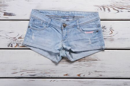 Light blue denim shorts. Short shorts on wooden background. New item from jeans store. Girls garment sold at discount. Stock Photo