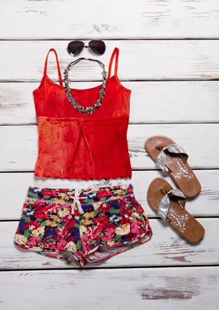 Beachwear and accessories for a young girl. Bright multi-colored summer shirt, shorts and accessories.