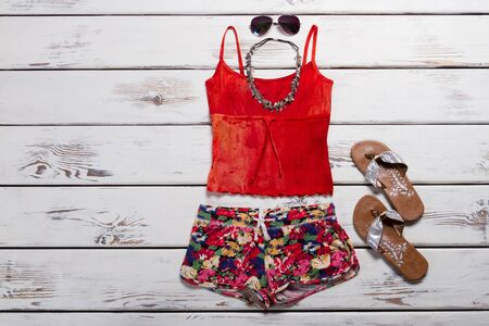 Beachwear and accessories for a young girl. Bright multi-colored summer shirt, shorts, flip flops, sunglasses and necklace.