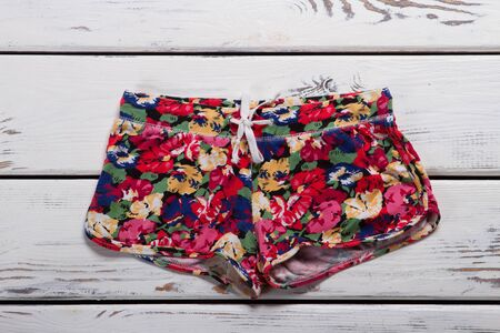 Summer shorts with floral print on a wooden background. Summer clothes for young girls.