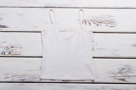 White top on wooden boards. Summer womens tank top.
