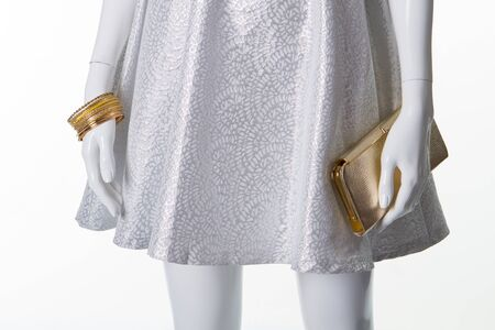 Silvery dress with accessories on a white mannequin. Skirt with gold bracelets and clutch.