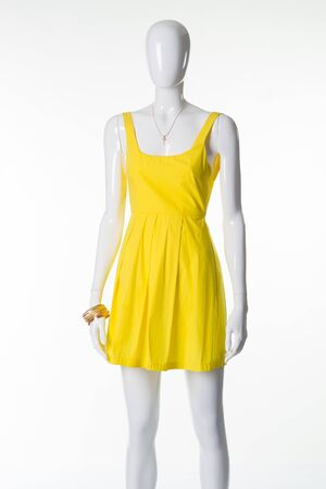 Mannequin in a yellow summer sundress. Sale of summer womens collection. Bright yellow dress trend of the season.