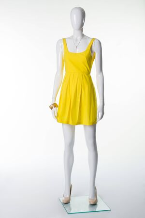 Mannequin in a yellow summer dress and  beige shoes with heels. Fashion yellow dress. Sale summer womens collection.