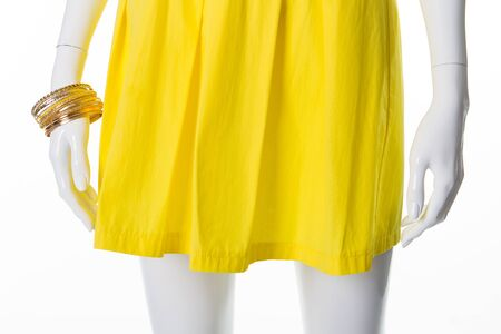 Bright summer yellow dress and gold bracelets on a mannequin. Summer dress and accessories.