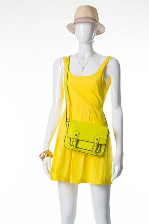 Mannequin in a yellow dress, straw hat and light green handbag. Summer sales. Mannequin for the storefront.