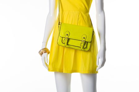 Mannequin in a bright yellow dress. Mannequin with yellow leather handbag. Yellow purse on female mannequin. Handbag with strap and accessories. Stock Photo