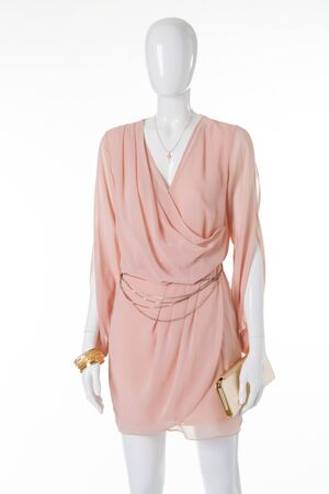 Light chiffon dress on a mannequin. Gently peach evening dress with gold accessories.