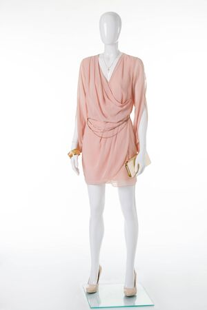 Delicate chiffon dress and beige high-heeled shoes. Golden clutch bag and accessories complement the gentle dress.