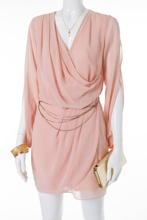 Beautiful evening dress with golden belt and clutch. Delicate pink chiffon dress on a mannequin.